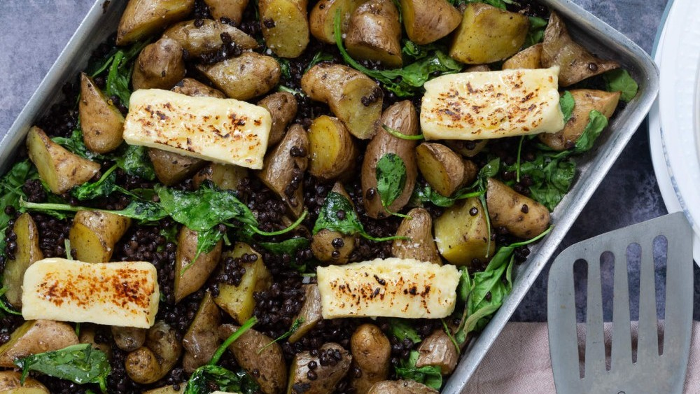 New potato, Puy lentils, spinach and halloumi traybake with honey