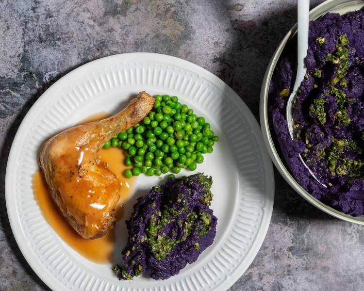 Purple mashed potato with salsa verde, served with roast chicken and peas